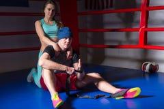 Молодая атлетическая поддержка женщины и боксер объятия мужской в боксерском ринге Стоковое Изображение RF