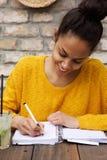 Молодая африканская дама сидя на таблице кафа и писать примечания Стоковые Фото