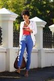 Молодая африканская женщина используя мобильный телефон outdoors Стоковая Фотография RF