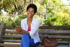 Молодая африканская женщина на скамейке в парке с сотовым телефоном Стоковые Фото