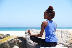 Молодая африканская женщина сидя на пляже в представлении йоги Стоковая Фотография