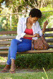 Молодая африканская женщина сидя на скамейке в парке с сумкой Стоковые Фотографии RF