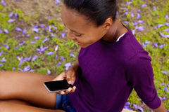 Молодая африканская женщина смотря мобильный телефон Стоковое Изображение