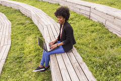 Молодая афро американская женщина используя компьтер-книжку Зеленые предпосылки casua Стоковые Фото