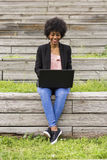 Молодая афро американская женщина используя компьтер-книжку Зеленые предпосылки casua Стоковые Изображения