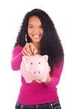 Молодая Афро-американская женщина кладя монетку в копилку Стоковые Изображения