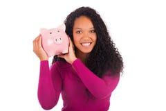Молодая Афро-американская женщина кладя монетку в копилку Стоковая Фотография RF