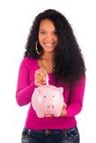Молодая Афро-американская женщина кладя монетку в копилку стоковое изображение rf