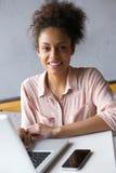 Молодая Афро-американская женщина работая на компьтер-книжке Стоковые Фотографии RF