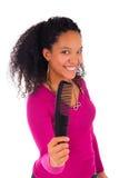 Молодая Афро-американская женщина расчесывая волосы стоковое фото