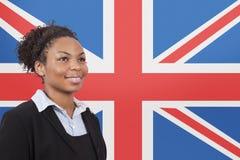 Молодая Афро-американская коммерсантка усмехаясь над флагом British стоковые изображения rf