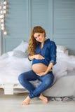 Молодая беременная женщина в джинсах Стоковая Фотография RF