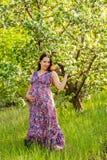 Молодая беременная женщина в зацветая саде стоковое фото rf
