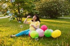 Молодая беременная женщина в парке Стоковое Изображение