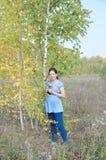 Молодая беременная женщина в поле около дерева березы Стоковые Изображения RF