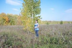 Молодая беременная женщина в поле около дерева березы Стоковая Фотография