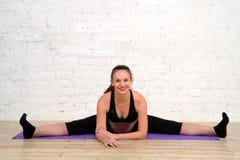 Молодая беременная женщина делая протягивающ шпагат работает на циновке йоги стоковые фото