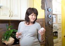 Молодая беременная женщина принимая пилюльки, Стоковые Изображения RF