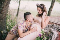 Молодая беременная женщина при ее супруг сидя около озера Стоковая Фотография RF