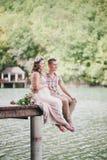 Молодая беременная женщина при ее супруг сидя около озера Стоковые Фотографии RF