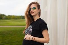 Молодая беременная женщина стоя на стене Стоковая Фотография