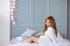 Молодая беременная женщина с усмехаться вьющиеся волосы Стоковая Фотография RF