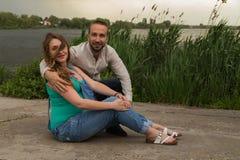 Молодая беременная пара на речном береге Стоковые Изображения