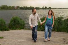 Молодая беременная пара на речном береге Стоковое Изображение RF