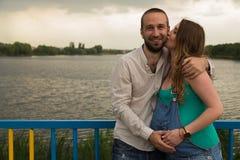 Молодая беременная пара на речном береге Стоковая Фотография