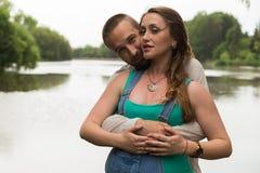Молодая беременная пара на речном береге Стоковое Изображение