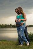 Молодая беременная пара на речном береге Стоковое фото RF