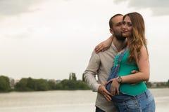 Молодая беременная пара на речном береге Стоковая Фотография RF
