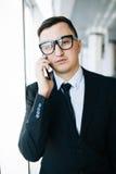 Молодая беседа бизнесмена на телефоне против окон Стоковая Фотография RF