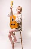 Молодая белокурая дама в сером свитере сидя на стуле и играя акустическую гитару Стоковая Фотография
