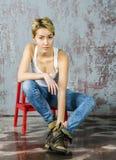 Молодая белокурая девушка с короткими волосами в куртке и джинсах джинсовой ткани сидит и смотрит Стоковые Фото