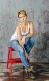Молодая белокурая девушка с короткими волосами в куртке и джинсах джинсовой ткани сидит и смотрит Стоковое Изображение RF