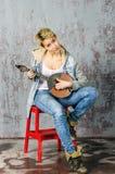 Молодая белокурая девушка с короткими волосами в куртке и джинсах джинсовой ткани сидит и смотрит с dombra Стоковые Изображения RF