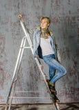 Молодая белокурая девушка с короткими волосами в куртке и джинсах джинсовой ткани сидит и смотрит Стоковая Фотография