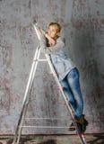 Молодая белокурая девушка с короткими волосами в куртке и джинсах джинсовой ткани сидит и смотрит Стоковые Изображения