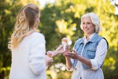 Молодая белокурая женщина давая мороженое к ее матери Стоковая Фотография RF