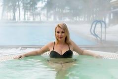Молодая белокурая женщина в джакузи ванны outdoors на зиме Стоковые Фотографии RF