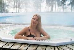 Молодая белокурая женщина в джакузи ванны outdoors на зиме Стоковая Фотография RF