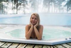 Молодая белокурая женщина в джакузи ванны outdoors на зиме Стоковые Изображения