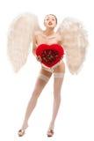 Молодая белокурая женщина в костюме ангела держа сердце Стоковое Фото