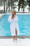 Молодая белокурая женщина в купальном халате около открытого бассейна на зиме Стоковая Фотография