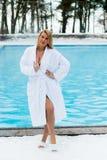 Молодая белокурая женщина в купальном халате около открытого бассейна на зиме Стоковое Изображение