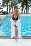 Молодая белокурая женщина в купальном халате около открытого бассейна на зиме Стоковые Изображения