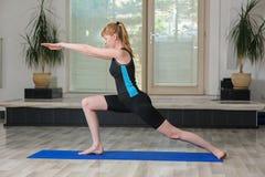 Молодая белокурая женщина делая тренировки гимнастики Стоковые Изображения RF