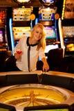 Молодая белокурая женщина играя рулетку в казино и выигрывать стоковые фотографии rf