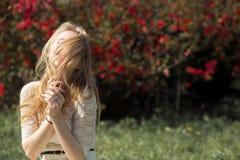 Молодая белокурая женщина наслаждаясь садом ароматности зацветая в воздухе Она глаза закрыто волосами от удовольствия стоковая фотография rf